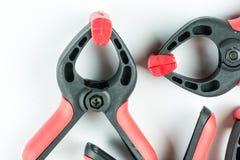 Röda och svarta plast- snickare klämmer hjälpmedel plana lägger ovanför vit bakgrund Fotografering för Bildbyråer