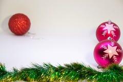 Röda och två rosa julbollar och julgarnering på en vit bakgrund Arkivfoton