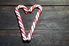 Röda och vita godisrottingar som bildar en hjärta på en bakgrund av mörka träplankor close upp behandla som ett barn fotoet för m stock illustrationer