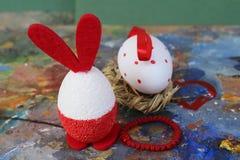 Röda och vita kaninägg för påsk på den gamla färgrika konstnärliga träpaletten royaltyfri foto