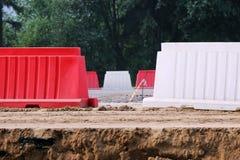 Röda och vita plast- barriärer som blockerar vägen arkivfoton