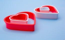 Röda och vita plast- hjärtor för lyckliga Valentins dag royaltyfria bilder