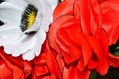 Röda och vita plast- konstgjorda härliga dekorativa ljusa blommor Arkivbilder