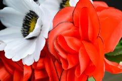 Röda och vita plast- konstgjorda ljusa härliga dekorativa ljusa blommor Royaltyfri Foto