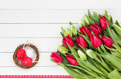 Röda och vita tulpan och dekorativa påskägg i litet rede på den vita tabellen Top beskådar Royaltyfri Bild