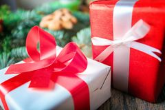 Röda och vitgåvor bredvid kakor och en sörja förgrena sig på en träbakgrund Jul som shoppar begrepp Royaltyfria Foton