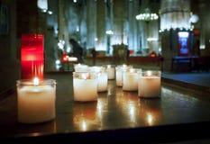 Röda och vitstearinljus i den gamla gotiska kyrkan och besökare på b Royaltyfria Foton