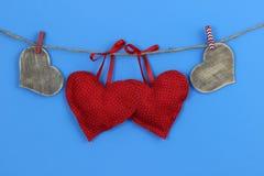 Röda och wood hjärtor som hänger på klädstreck med blå bakgrund Fotografering för Bildbyråer