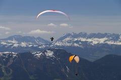 röda orange over paragliders för berg Arkivbild