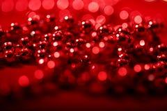 Röda pärlor med suddig ljusbokeh för julatmosfär Fotografering för Bildbyråer