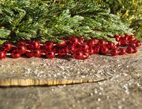 Röda pärlor och barrträdfilialer på en bakgrund av lantligt trä royaltyfri bild