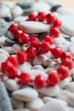 Röda pärlor på kiselstenar Arkivfoton