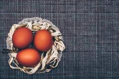 Röda påskägg i ett dekorativt rede på en brun bakgrund arkivfoto