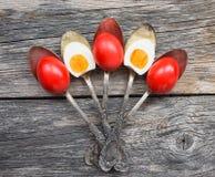 Röda påskägg i gamla tappningskedar på träbakgrund Royaltyfri Fotografi