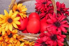 Röda påskägg ligger i en korg med blommor, på en träbakgrund arkivfoto