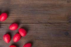 Röda påskägg på träbakgrund royaltyfria foton