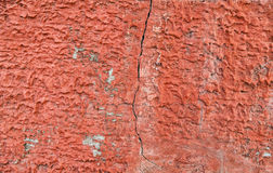 Röda packade väggar med sprickor och oriktigheter Arkivfoton