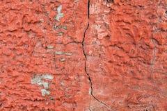 Röda packade väggar med sprickor och oriktigheter Arkivfoto