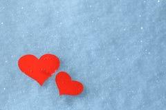 Röda pappers- hjärtor i snön valentin för kortdaghälsning s Arkivfoto