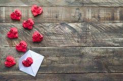 Röda pappers- hjärtor med det vita kuvertet på träbakgrund avstånd Arkivfoto