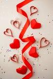 Röda pappers- hjärtor och siden- band, konfettier på grå bakgrund Valentin dagabsctract Symbol av förälskelse Kopieringsutrymme,  royaltyfri bild