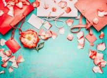 Röda pappers- shoppingpåsar med blommor på ljus - sjaskig chic bakgrund för blå turkos, bästa sikt, ställe för text, gräns Sommar arkivbilder