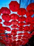 Röda paraplyer i luften Royaltyfri Bild