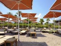 Röda paraplyer och tomma dagdrivare på en sand sätter på land Royaltyfri Fotografi