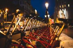 Röda parkerade uthyrnings- cyklar på nattperspektivskottet royaltyfri bild