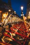 Röda parkerade uthyrnings- cyklar på nattperspektivskottet royaltyfria bilder
