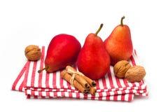 Röda pears på randig tablecloth Royaltyfri Foto