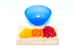 Röda peppar för orange guling som skivas på en skärbräda med blått, bowlar Arkivbilder