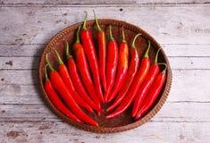 Röda peppar i den tröska korgen Arkivfoton