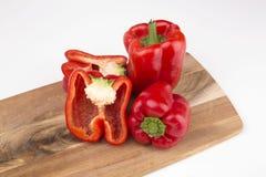 Röda peppar med brädet som isoleras på vit bakgrund Royaltyfria Bilder