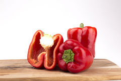 Röda peppar med brädet som isoleras på vit bakgrund Arkivbilder