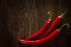 Röda peppar på den bruna tabellen Varma peppar på träbakgrund Bakgrund för chilipeppar med kopieringsutrymme Royaltyfri Bild