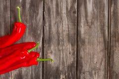 Röda peppar på trä royaltyfri fotografi
