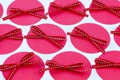 Röda pilbågar på rosa prickar Royaltyfri Bild