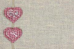 Röda pläd- och trähjärtor gränsar sjaskig säckvävbakgrund Royaltyfria Bilder