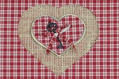 Röda pläd- och trähjärtor med sjaskig säckväv- och plädbakgrund Royaltyfri Foto