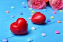 Röda plast- hjärtor och rosor på träbakgrund arkivbild