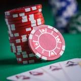 Röda pokerchiper som staplas på den gröna tabellen Arkivbild