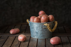 Röda potatisar i hink på den gamla tabellen fotografering för bildbyråer