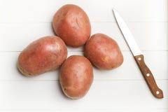 Röda potatisar och en kniv Arkivbilder