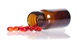 Röda preventivpillerar en preventivpillerflaska Royaltyfri Fotografi