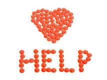 Röda preventivpillerar som är ordnade i hjärta, formar med hjälptecknet. Royaltyfria Foton