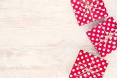 Röda prickiga gåvaaskar spridde över vit wood bakgrund kopiera avstånd Royaltyfria Foton