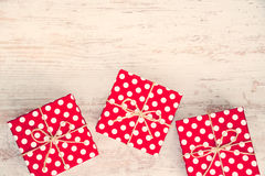 Röda prickiga gåvaaskar spridde över vit wood bakgrund Tappningeffekt Arkivbilder