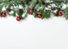 Röda prydnader för snöig jul som hänger i granträdfilialer royaltyfri bild