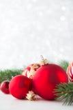 Röda prydnader och xmas-trädet blänker på feriebakgrund Glad julkort Arkivbild